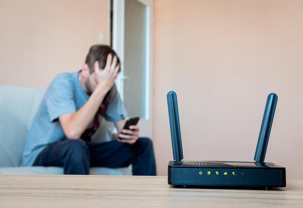hombre agarrándose la cabeza con su celular adelante un router